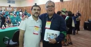 Diretor da APUG e Delegado da seção sindical no CONAD, professor Antonio Netto, entregando ao presidente eleito e empossado Antonio Gonçalves, exemplar do livro publicado pela APUG.